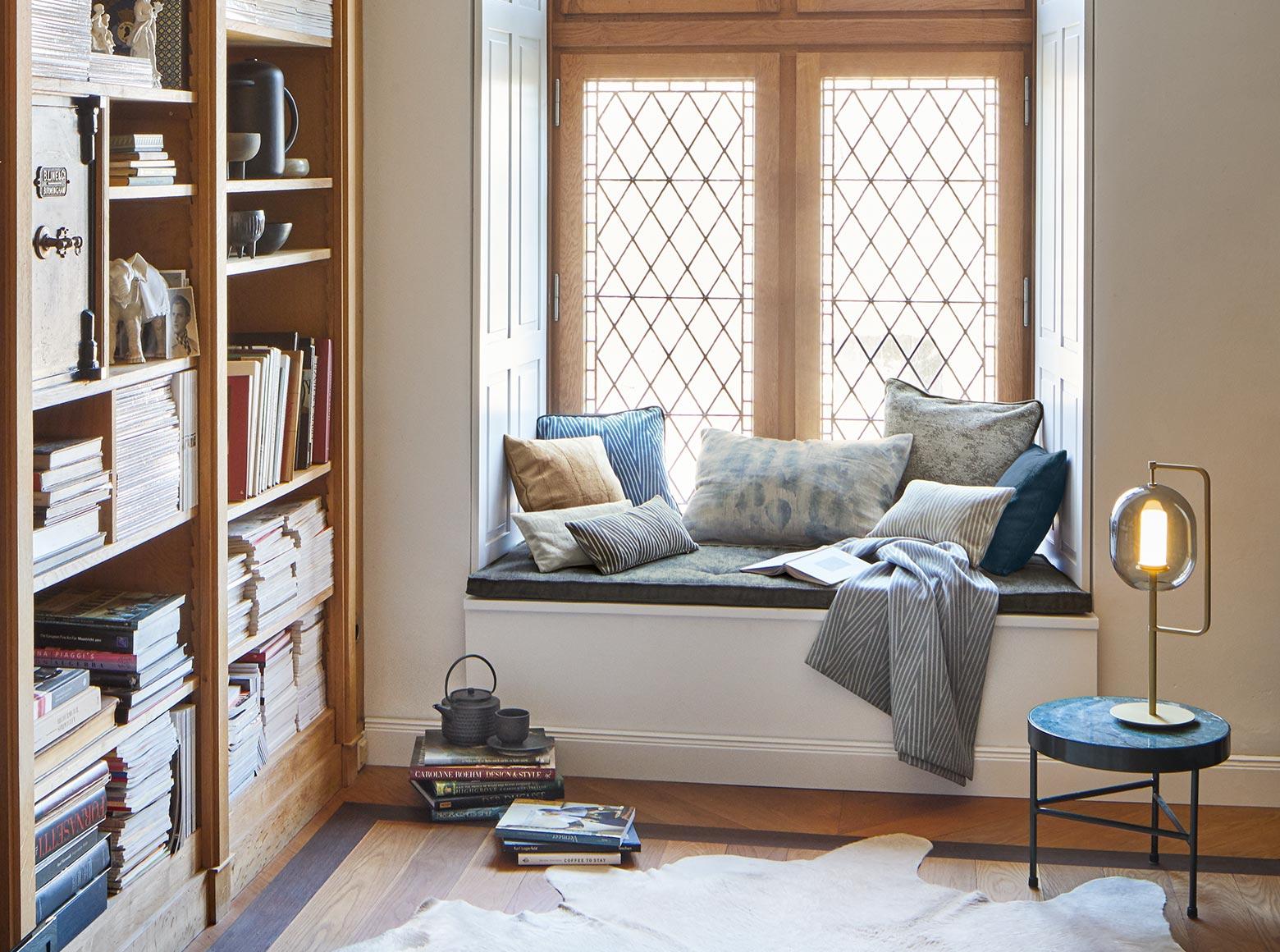 Eine gemütliche Ecke mit Plaids und Kissen um in Ruhe ein Buch oder die Zeitung zu lesen.